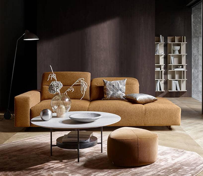 ciemna ściana zpaneli drewnianych zjasnymi półkami na książki oraz jasno brązowej kanapie