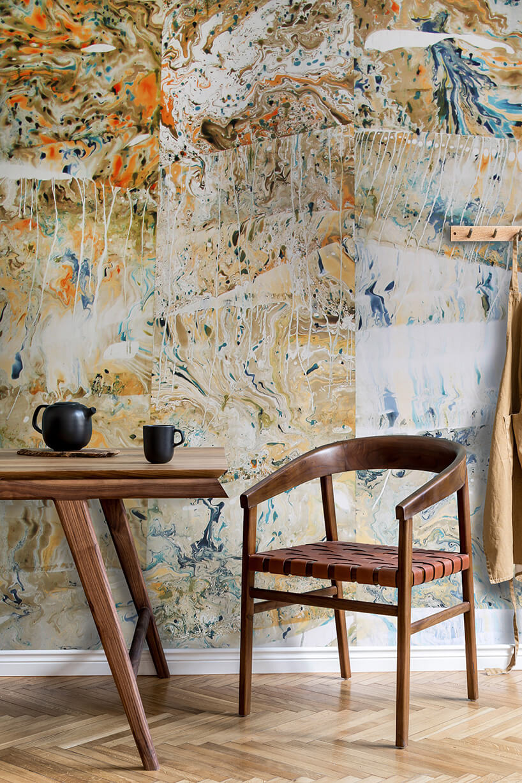 wzorzysta tapeta na ścianie przy której jest drewniany stolik zpochyłymi nogami oraz krzesło