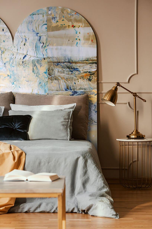 łóżko zszarą narzutą oraz brązowymi poduszkami obok miedzianej lampki