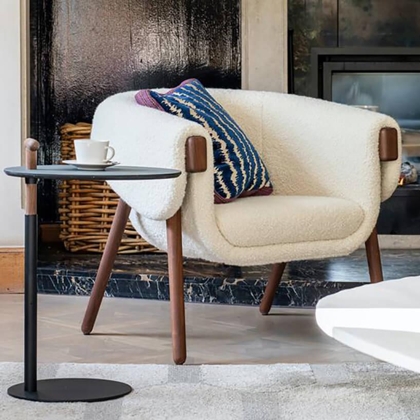 jasno kremowy niski fotel na drewnianych noga wlekko brązowym kolorze zpoduszką wniebieskie pasy