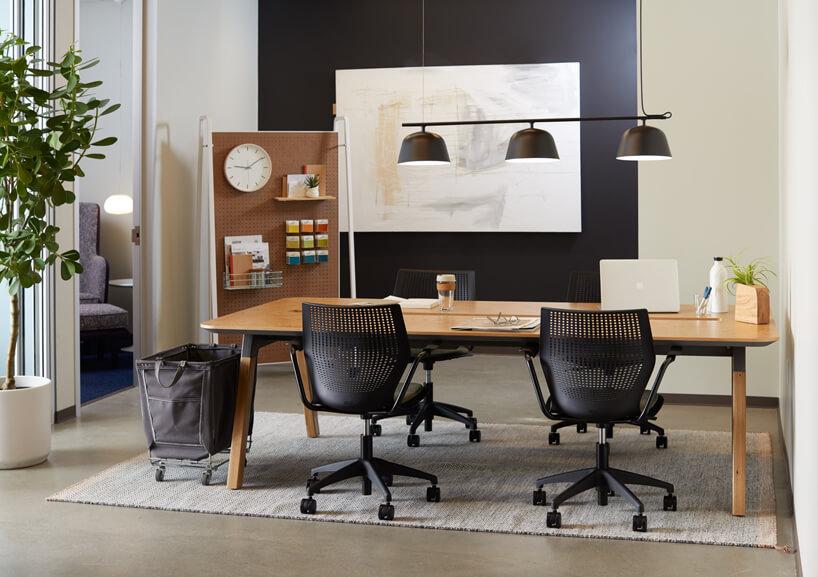 duże wspólne drewniane biurko zczterema czarnymi fotelami