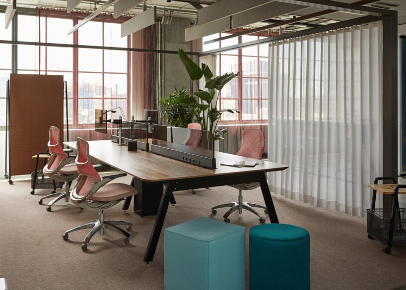 aranżacja biura open space zdużym biurkiem podzielonym ncztery stanowiska zczterem różowymi ergonomicznymi krzesłami