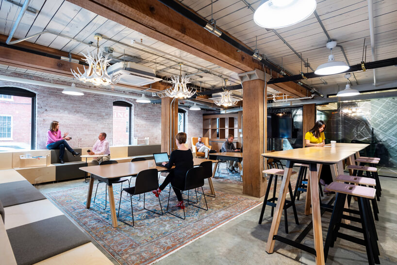 pracownicy waranżacji przestrzeni biurowej wbudynku zceglanymi ścianami drewnianym sufitem zdrewnianymi elementami konstrukcyjnymi