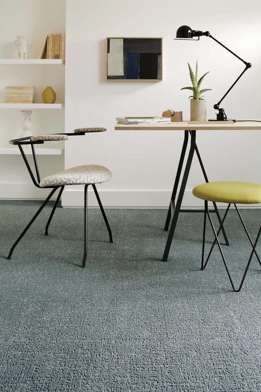 dwa siedziska zczarnym stelażem zcienkich metalowych prętów przy biurku zcienki drewnianym blatem