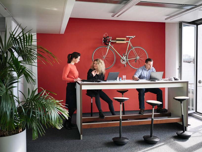 trzy osoby przy wysokim biurku zpodnóżkiem zSiedziska Stitz marki Wilkhahn na tle czerwonej ściany zpowieszonymi na niej rowerem