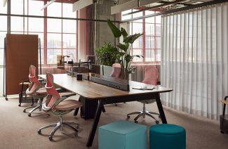 aranżacja biura open space z dużym biurkiem podzielonym n cztery stanowiska z czterem różowymi ergonomicznymi krzesłami