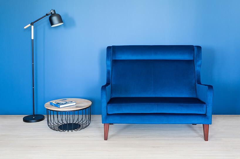 niebieska kanapa dwu osobowa na tle niebeiskiej ściany