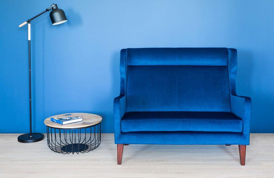 niebieski fotel obok stolika z prętów i drewnianego blatu na tle niebieskiej ściany