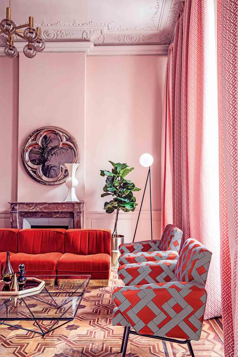 czerwona kanapa szaro czerwone fotele wróżowym pomieszczeniu zlustrem na ścianie