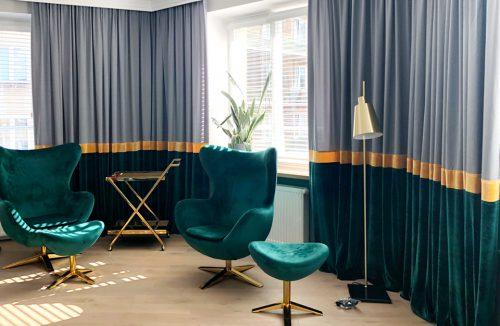 aranżacja salonu z zielonymi fotelami na tle długich srebrno-złoto-zielonych zasłon