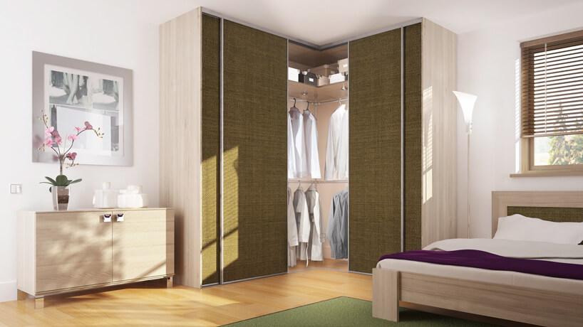 brązowa szafka na koszule brązowe łożko zbiałym materacem zielony dywan na drewnianych panelach