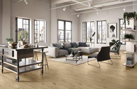 beżowa kanapa czarne krzesło stolik na drewnianych panelach