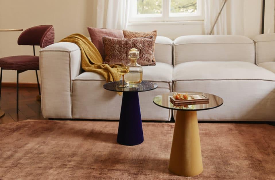 beżowa duża prostokątna kanapa przy dwóch stoliczkach szklanych w kolorze złotym oraz czarnym