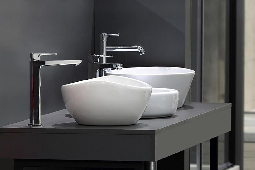 trzy rożne baterie łazienkowe przy wolnostojących umywalkach