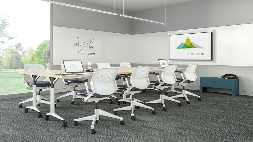 biało szara sala konferencyjna zdwoma stołami na kółkach iośmioma białymi krzesłami na kółkach zfioletowym siedziskiem