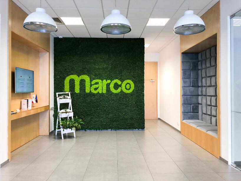 aranżacja wnętrza open space zzieloną ściana znapisem Marco obok miejsca do siedzenia osadzonego wścianie
