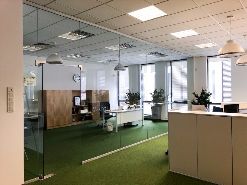biało zielona aranżacja open space zoddzielonym szkłem biurem