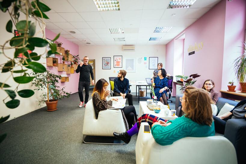 pracownicy podczas przerwy wbiało różowym pomieszczeniu zwyjątkowymi białymi fotelam