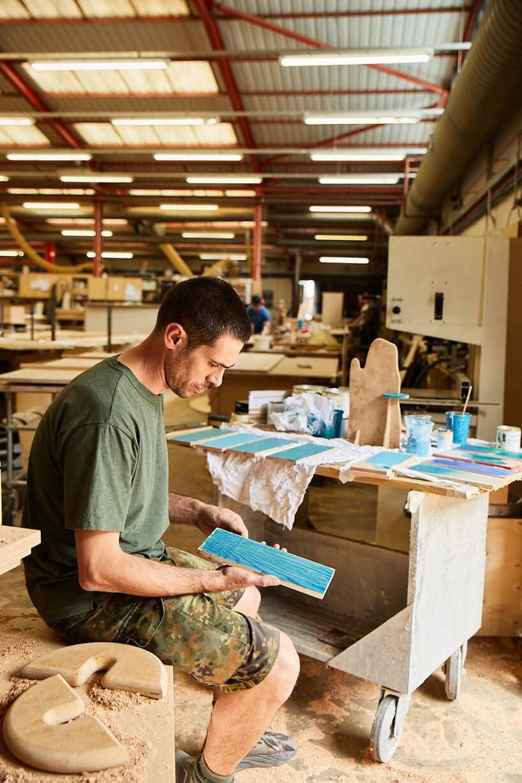 osoba wzielnej koszulce trzymająca kawałek deski wkolorze niebieskim na stolarni