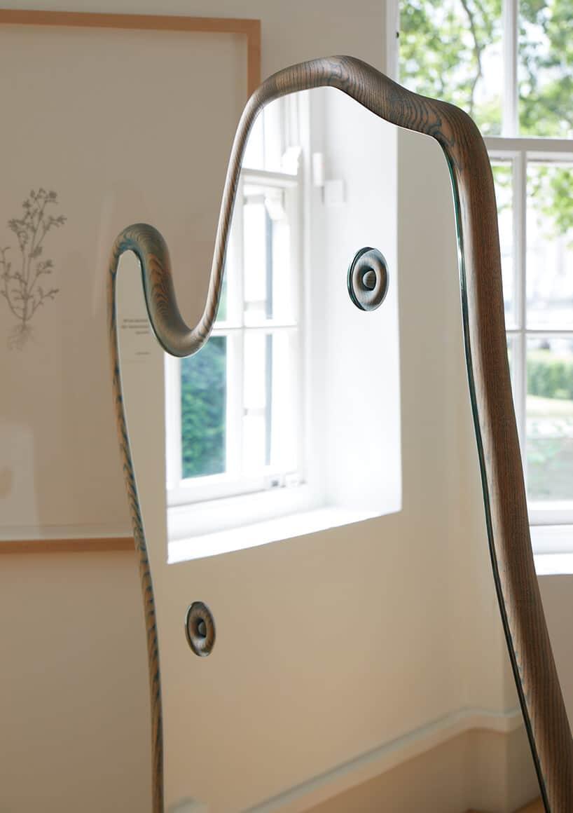lustro wfuturystycznym kształcie zodbiciem białego okna