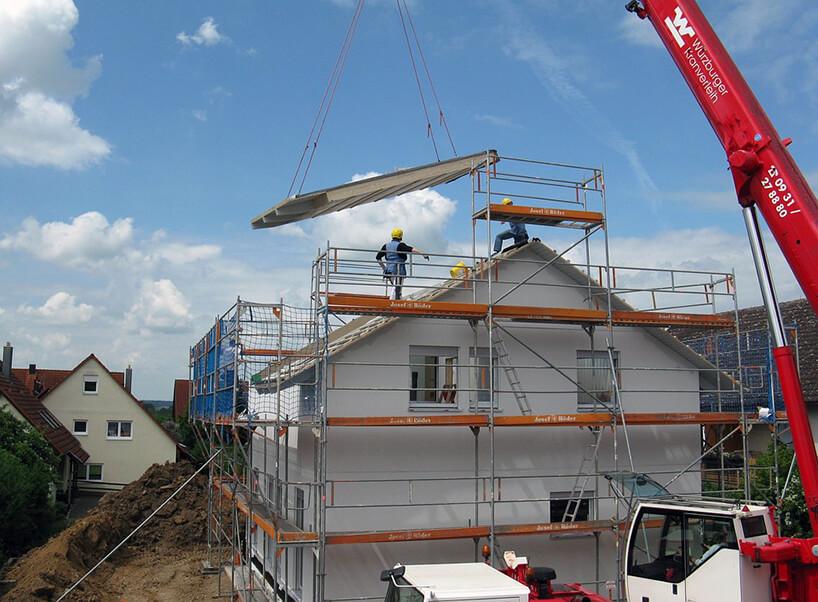 budowa domu jednorodzinnego podczas układania dachu czerwonym dźwigiem