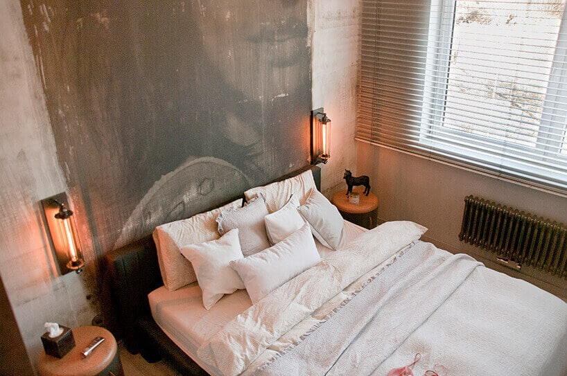 jasne wnętrze sypialni zfototapetą na ścianie oraz podłużnymi lampkami wkolorze czerwonym