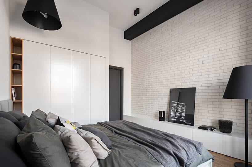jasne białe wnętrze sypialni zdodatkami wkolorze szarym wformie pościeli oraz drzwi atakże czarnej belki sufitowej