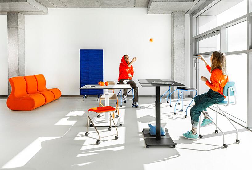 mobilne meble biurowe VANK_CO czarny ibiały stół obok siedzisk na kółkach na tle niebieskiej ścianki akustycznej na kółkach