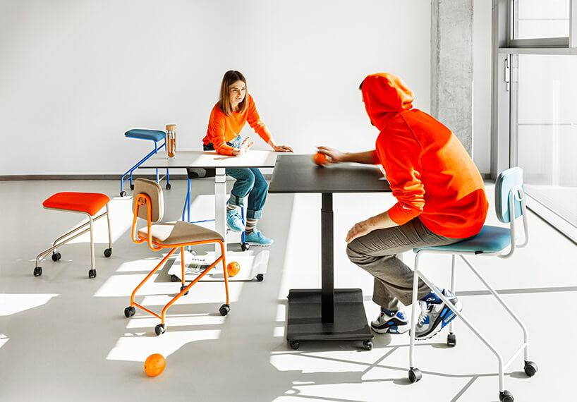 mobilne meble biurowe VANK_CO dwie osoby wpomarańczowych bluzach podczas zabawy pomarańczą na dwóch stołąch