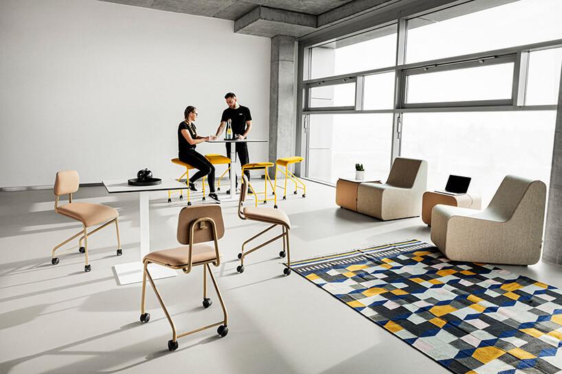 mobilne meble biurowe VANK_CO beżowe krzesła zkółkami na końcach nóg przy białym mobilnym stole