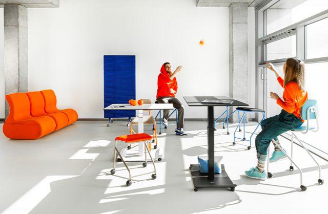 mobilne meble biurowe VANK_CO czarny i biały stół obok siedzisk na kółkach na tle niebieskiej ścianki akustycznej na kółkach