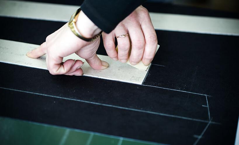 zjdęcie kobiecych dłoni podczas odrysowywania na czarnej powierzchni drewnianego szablonu