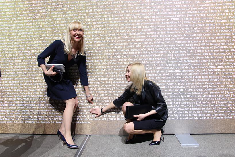 dwie kobiety wczarnych sukienkach pokazujące słowo VANK na dużej tablicy zróżnymi firmami