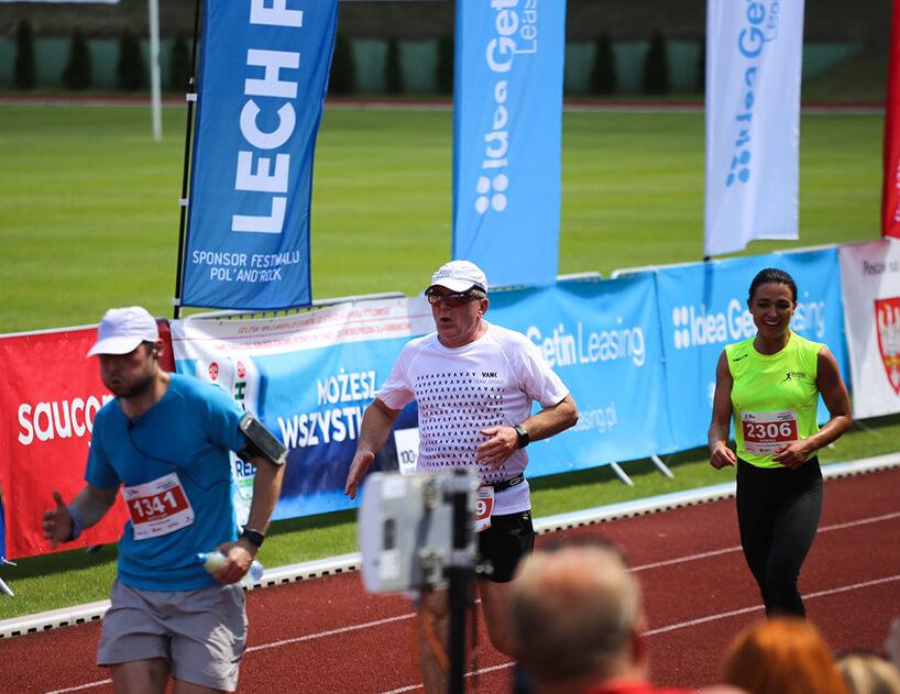 mężczyzna wbiałej koszulce VANK pośród innych biegaczy wtrakcie biegu na bieżni