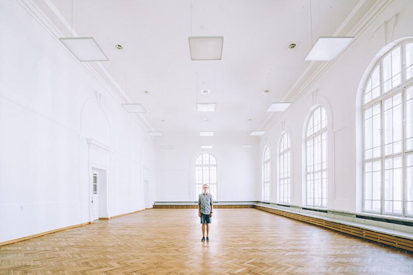 mężczyzna stojący wdużej białej sali zdrewnianym parkietem iwysokim oknami