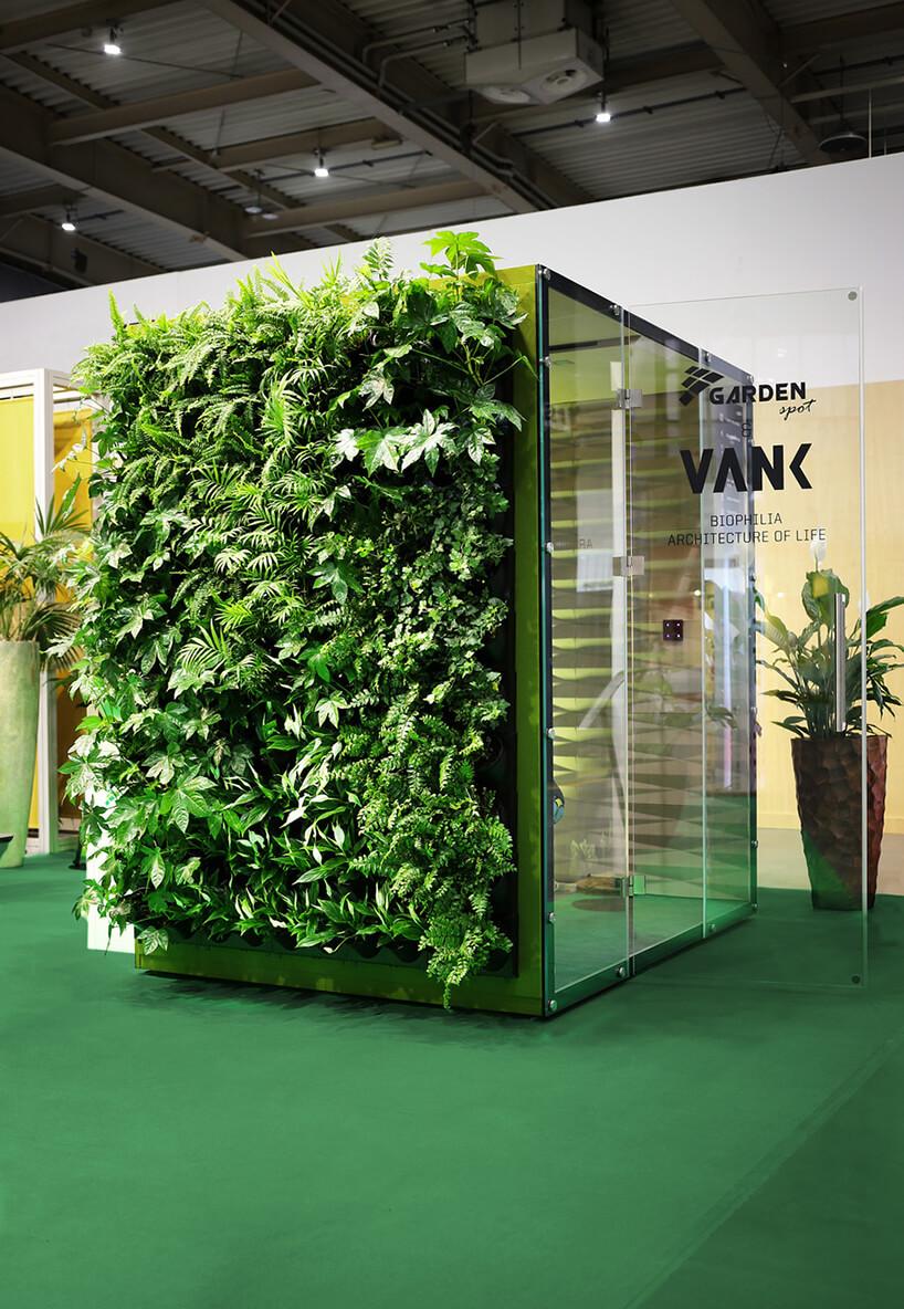 zielony box akustyczny VANK_WALL JUNGLE zotwartymi szklanymi drzwiami iroślinami na zewnętrznej ścianie