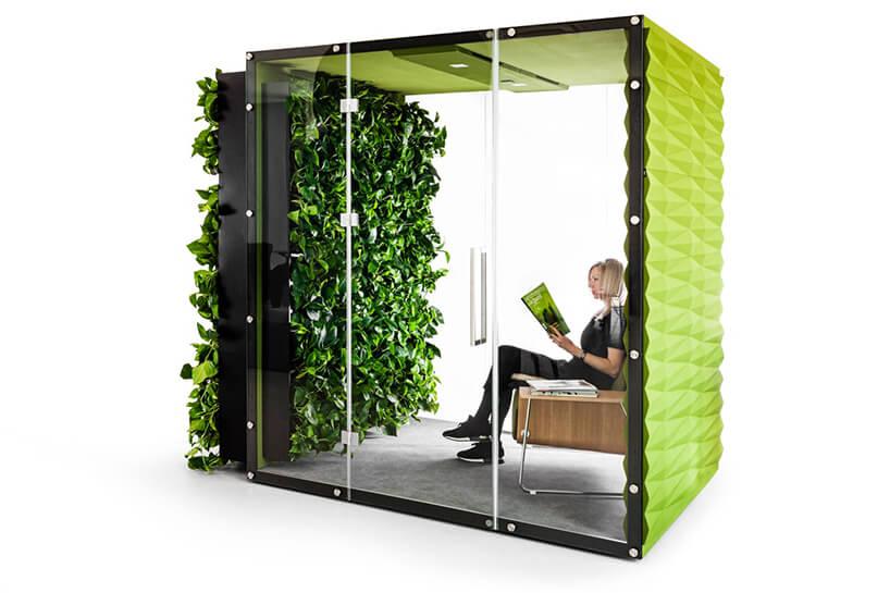 kobieta siedząca zielonym boxie akustycznym VANK_WALL JUNGLE zotwartymi szklanymi drzwiami iroślinami na zewnętrznej ścianie