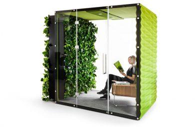 kobieta siedząca zielonym boxie akustycznym VANK_WALL JUNGLE z otwartymi szklanymi drzwiami i roślinami na zewnętrznej ścianie