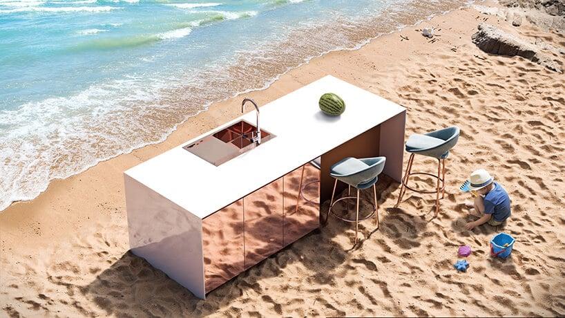 kuchnia zpołyskującym panele zróżem oraz białym blatem na plaży przy morzu ifalach