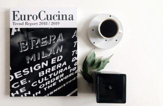 książka EuroCucina obok filiżanki z kawą oraz małego kwiatka