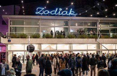 szary modernistyczny budynek z niebieskim neonem Zodiak nad głowami odwiedzających