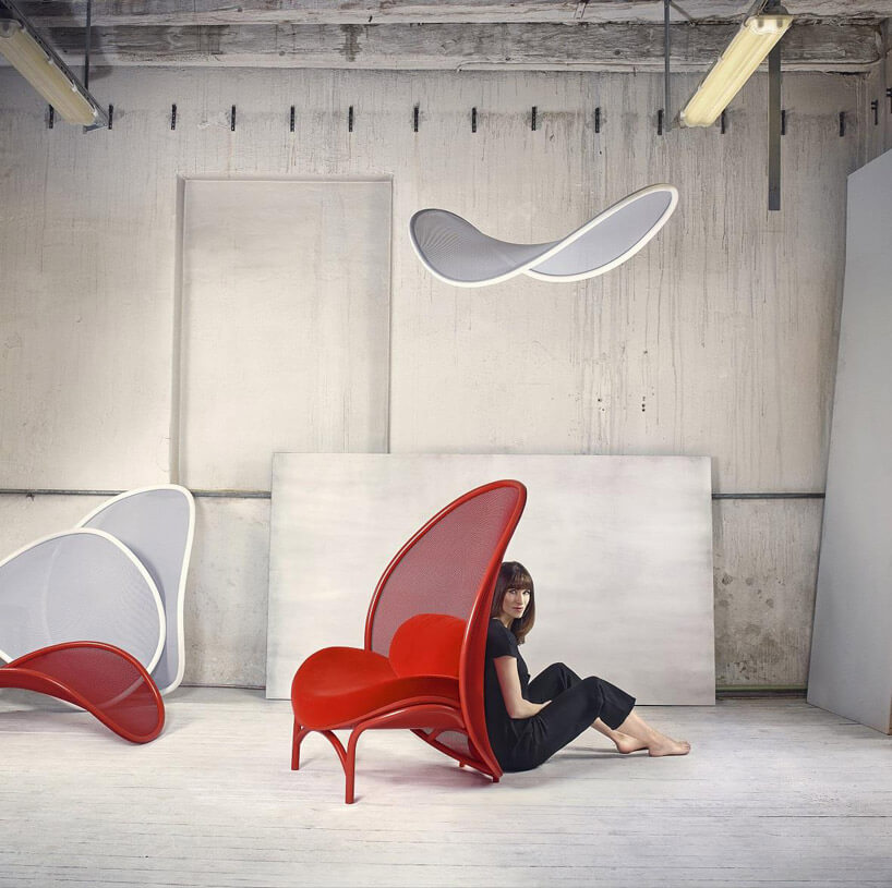 czerwone krzesło biały żyrandol kremowe ściany pani ubrana na czarno za krzesłem