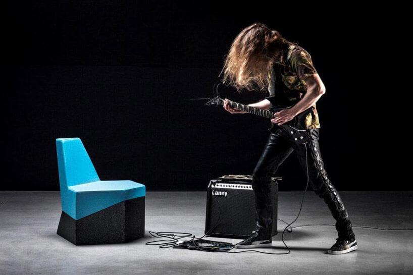 niebieskie krzesełko czarny wzmacniacz gitarzysta ubrany na czarno zczarną gitarą elektryczną wciemnym pomieszczeniu zszarą podłogą