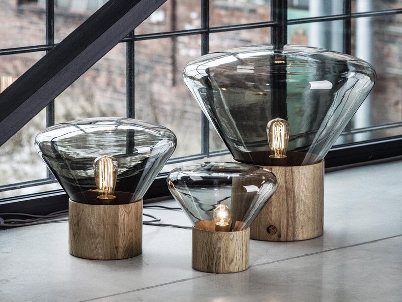 Szklane lampy wdrewnianym stojaku szyby wtle białe płytki
