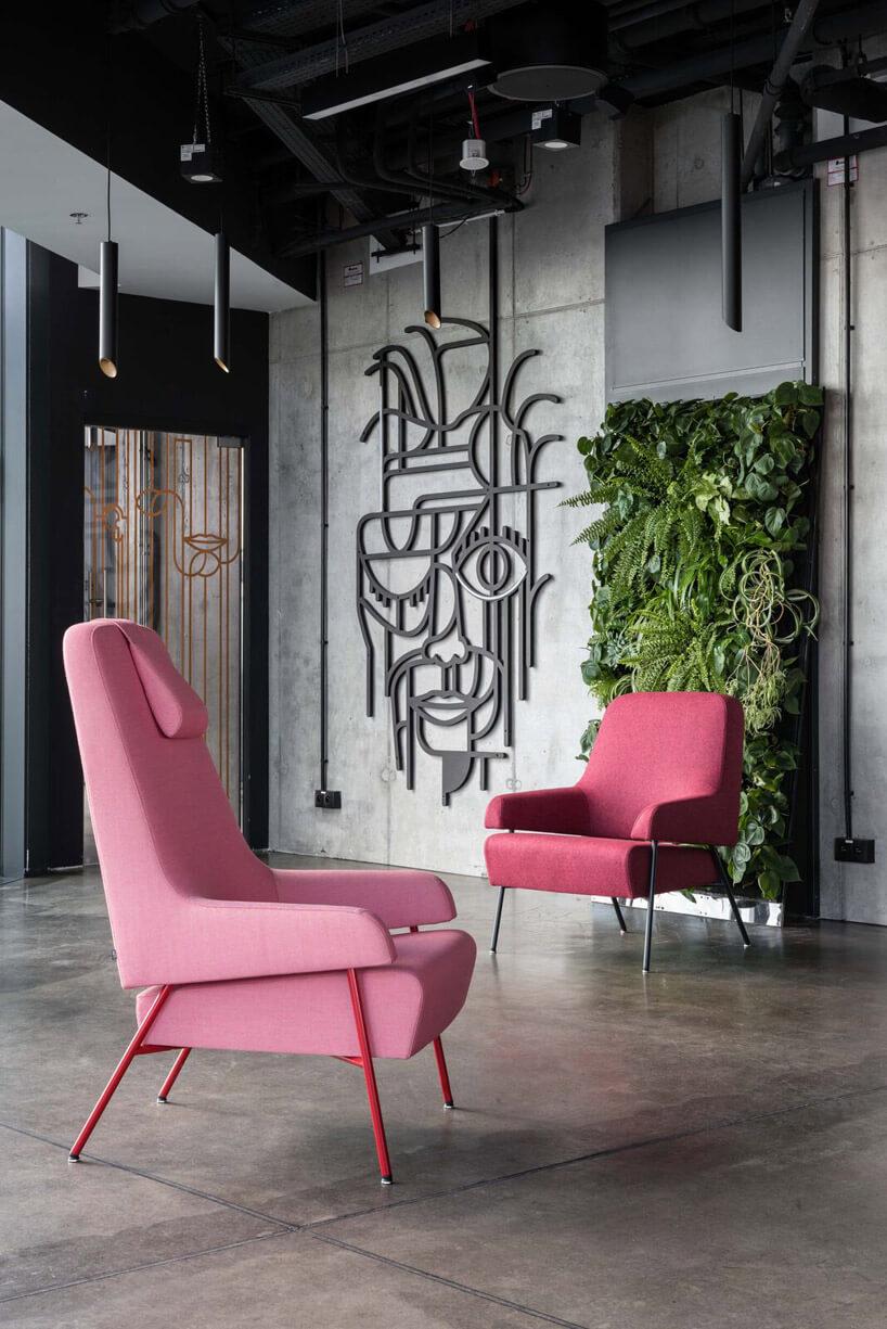 różowe fotele zieleń wtle na ścianie biała ściana zrysunkiem brązowa podłoga