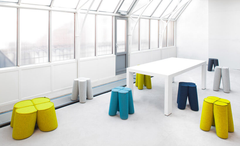 żółte granatowe ibiałe taborety zbiałym stołem biała podłoga szklane szyby ibiałe ściany