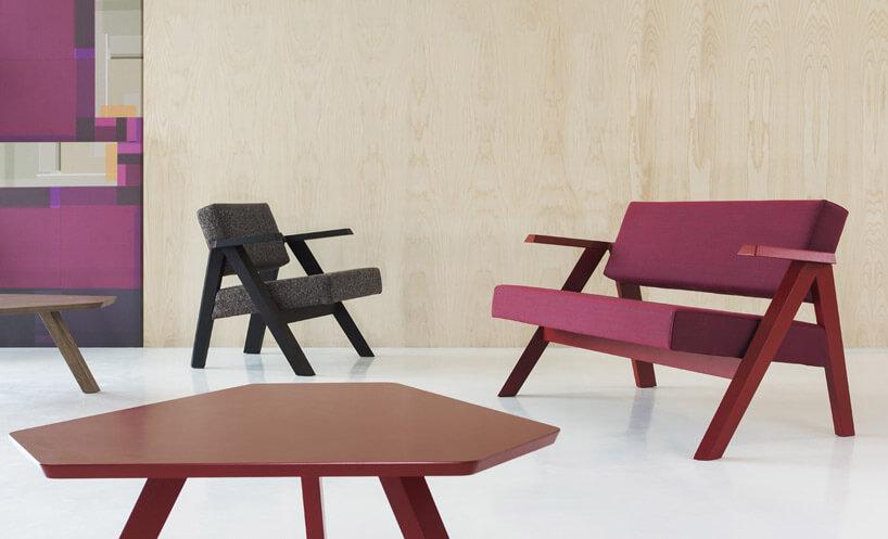 czarny fotel czerwona ławka brązowy stolik kremowa ściana biała podłoga