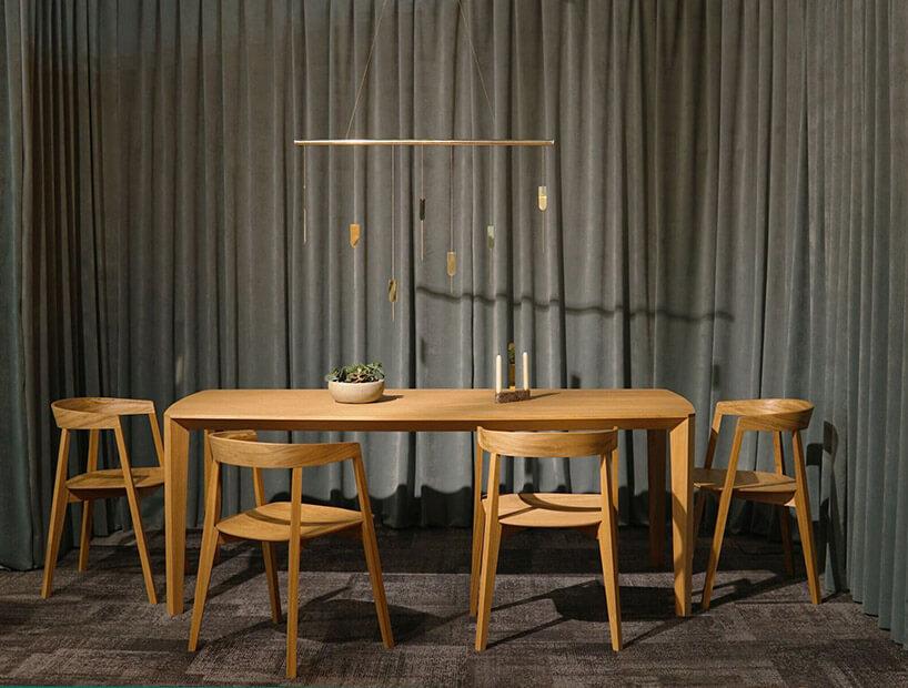 drewniany stół icztery krzesła na tle szarej kotary