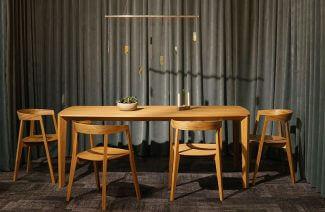 drewniany stół i cztery krzesła na tle szarej kotary