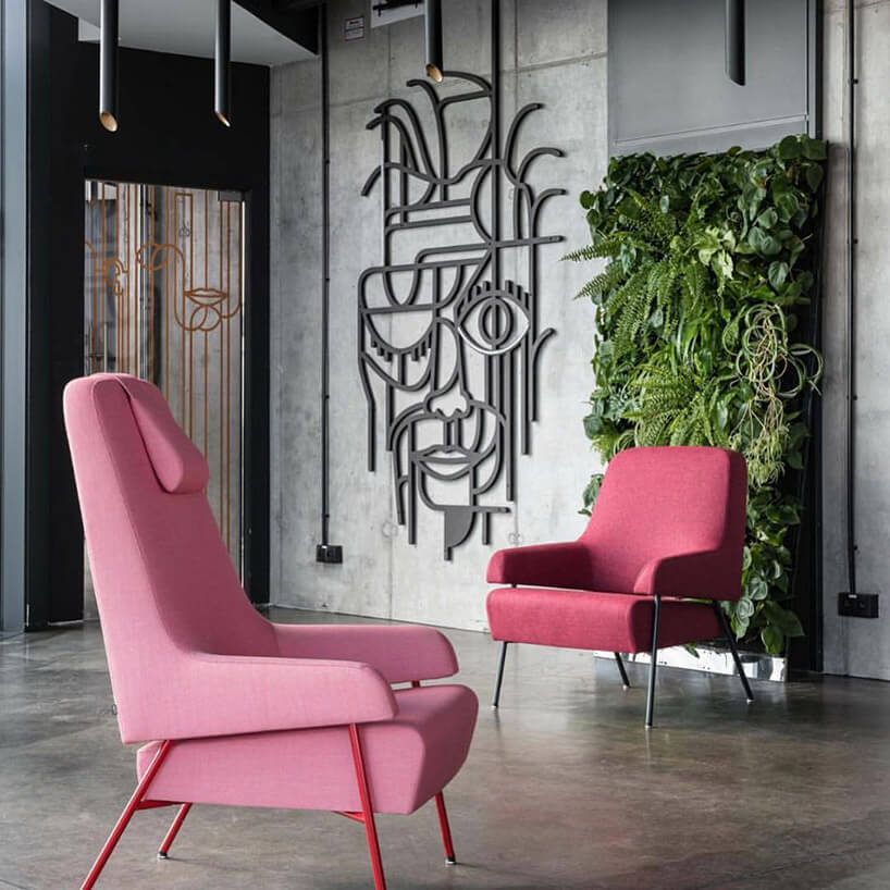 swa różowe fotele we szarym wnętrzu zżywą ścianką